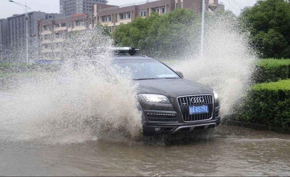 汽车疾驶而过,溅起巨大的水花.