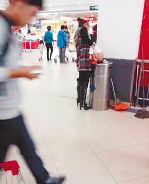 哈尔滨一女子扶小孩家乐福超市垃圾桶上当众大便引