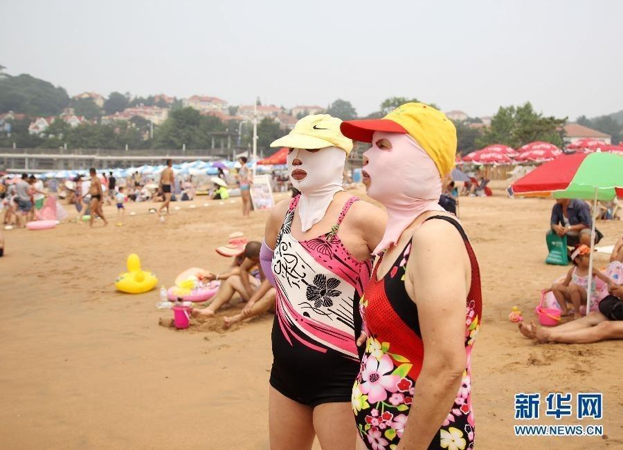 """在青岛第一海水浴场,游泳的人们戴上""""脸基尼""""防晒."""