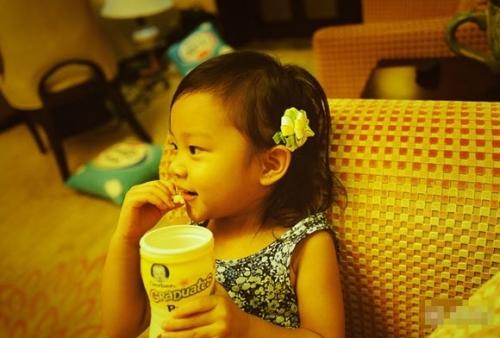 照片中甜馨耳边戴着一朵小纸花,笑嘻嘻的吃着零食非常的可爱.