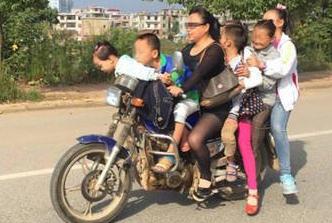 惊险一幕:女子骑摩托车载一家七口上街