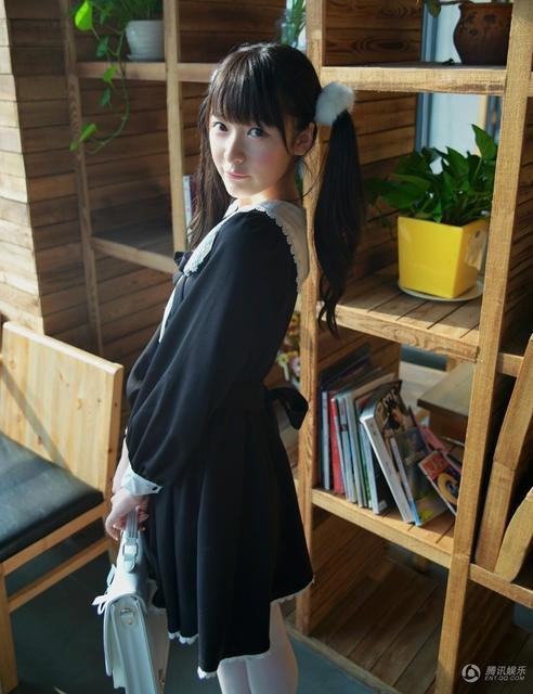照片中,徐娇扎着双马尾,身穿一身可爱的萝莉风黑色长裙,坐在咖啡店里