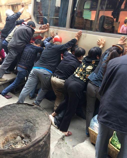 重庆老人被卷入车轮受伤 市民抬车救人