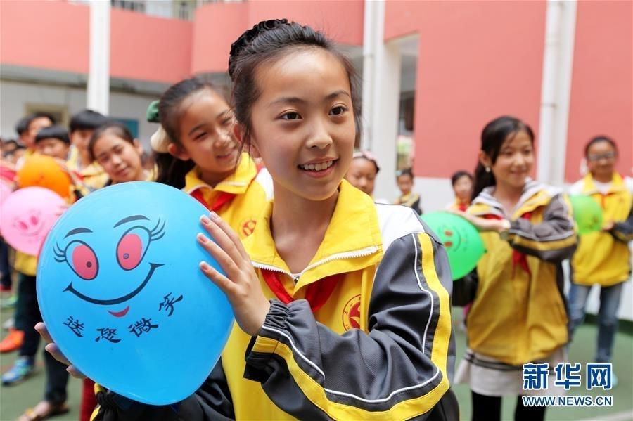"""小学生们利用""""笑脸""""气球进行""""传递微笑""""互动游戏,自编了""""笑脸""""气球操."""