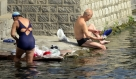 图为市民在泉水中洗刷衣物。
