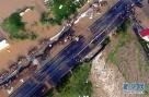 7月21日,抗洪人员在漫水路段抢险。当日,由于长江支流府澴河快速上涨,位于湖北省孝感市境内的107国道八一大桥段出现漫堤,交通中断。当地组织力量筑堤,保卫国道。新华社记者 程敏 摄