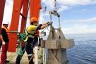 """8月14日,""""张謇""""号上的工作人员用箱式采样器采集海底沉积物。 新华社记者 张建松 摄"""