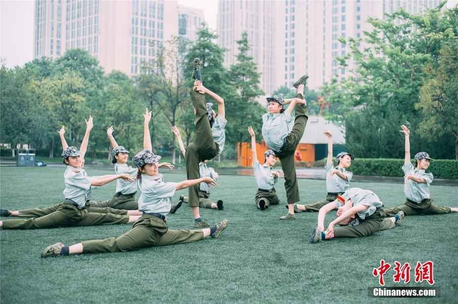 """9月是大学新生军训的日子。近日,重庆大学艺术学院舞蹈表演专业的新生在军训间隙秀起了高难度舞蹈动作。据了解,这是她们在军训休息时的""""娱乐活动"""",既练习基本功,也能靠舞蹈增进同学之间的感情。洪成骐 摄"""