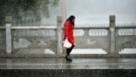 10月27日,在宁夏青铜峡市,一名行人冒雪从桥上走过。当日,宁夏回族自治区迎来入秋后首场全区性降雪天气,并伴有5到6级西北风。宁夏气象台发布暴雪蓝色预警信号,提醒相关部门和行人做好防范工作。新华社记者 李然 摄