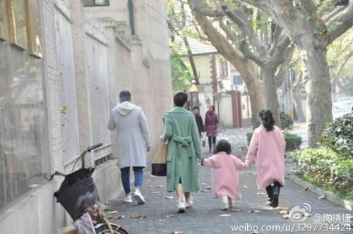 文章马伊琍一家人均穿浅色大衣,马伊琍牵着两个女儿,过马路时,文章抱
