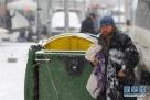 1月10日,在马其顿斯科普里,一名流浪汉在下雪天寻找御寒衣物。