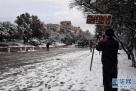 1月10日,在希腊雅典,一名男子在大雪后对着雅典卫城拍照。