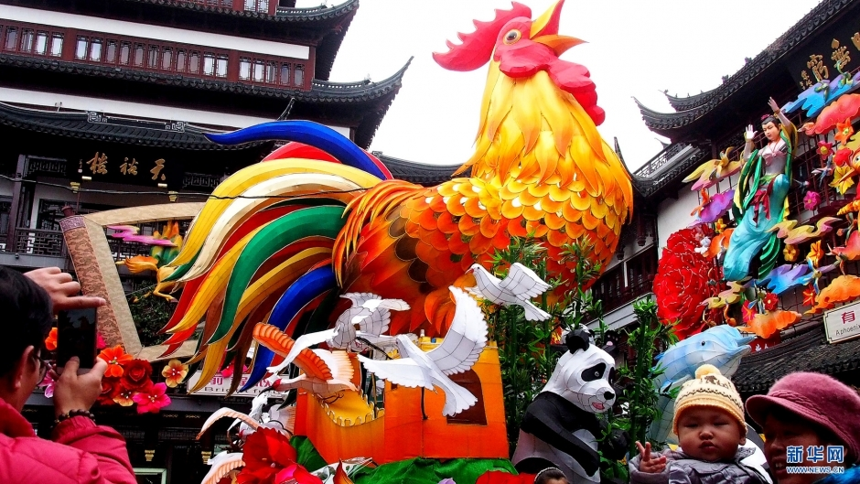 """1月15日,游客在上海市城隍庙景区内和""""雄鸡报晓""""彩灯合影。随着春节脚步的临近,火红的灯笼、喜庆的春联、憨态可掬的鸡饰品纷纷亮相上海街头,节日的喜庆气氛日渐浓郁。 新华社记者 陈飞 摄"""
