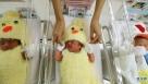 1月3日,在泰国曼谷,护士正在照顾身着小鸡服装的婴儿。