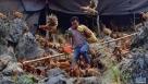 在广西大化瑶族自治县七百弄乡弄雄村,贫困户蓝旺明在鸡舍里准备给七百弄鸡喂食玉米。七百弄鸡养殖是大化县重要的脱贫产业(1月6日摄)。新华社记者黄孝邦摄