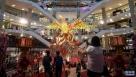 1月11日,在马来西亚吉隆坡,顾客经过一家购物中心内公鸡造型的灯光装置。