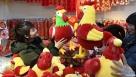 """1月16日,市民在南京沃尔玛超市的春节饰品销售区选购绒布鸡。近日,南京市各大零售商将春节商品投入销售,吸引市民前来选购。除大型超市的促销活动,南京举办的各类春节食品商品交易会、年货集市以及电商""""年货节""""等活动也为市民提供了丰富的春节商品。新华社记者 孙参 摄"""