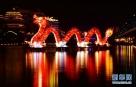 """这是2月7日在湖北省宣恩县贡水河畔拍摄的""""龙戏水""""造型彩灯。  元宵节临近,各地因地制宜,在街头、河道、广场等处布置璀璨花灯,霓虹闪烁,流光溢彩,营造出浓浓的节日氛围。  新华社发(宋文 摄)"""