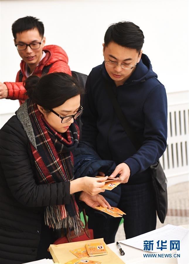 3月1日,在北京人民大会堂澳门厅,参加十二届全国人大五次会议采访报道的记者领取证件。 新华社记者赵颖全摄