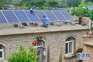 电力技术人员在河北省衡水市武邑县东五更村一农户房顶检修分布式光伏发电设备(2016年8月25日摄)。