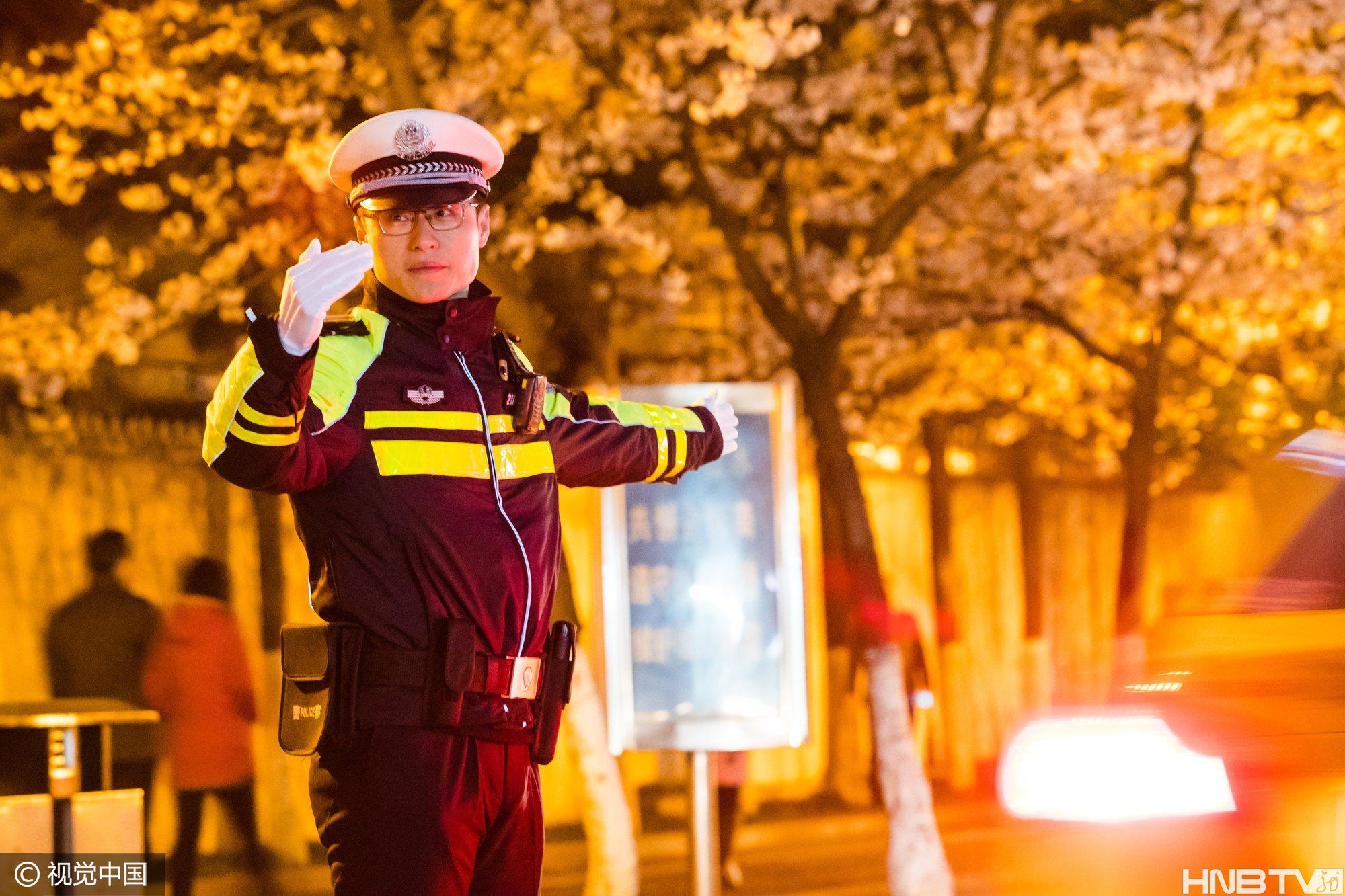 南京:交警夜幕下值勤 与樱花相映成景