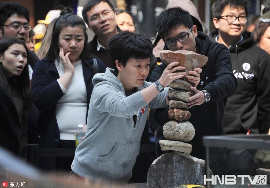 """2017年3月26日,上海。不用胶水,不用钉子,不用粘合剂,单单凭借纯手工技艺和神奇的重力平衡襄助,一堆碎石能够顶起辆一吨多重的汽车,你见过没?当日,在上海新天地就出现了这样一个""""不可思议""""的重力平衡艺术装置:近十块大小迥异的石头以近乎不可能的堆叠方式,稳稳支撑起一辆汽车,这个装置作品由加拿大平衡艺术家迈克尔-格拉布完成。展示现场也设置了小型的模拟堆搭台,让游客也来试一试自己的平衡能力,是否可达到这样的顶车效果。"""