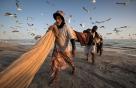 摄影师艾哈迈德·穆罕默德·阿尔托奇与渔民在一起度过了许多清晨,拍摄下了二月份佐法尔省渔民趁着沙丁鱼洄游进行捕捞的情形。