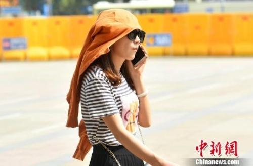 图为市民用衣物遮阳。 吕明 摄