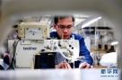 雄安新区容城县一服装企业的工人在生产车间工作(4月5日摄)。